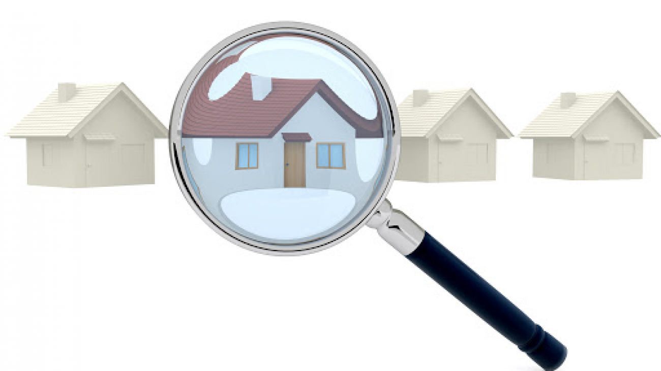 Looking for a house through a magnifying glass - isolated over white